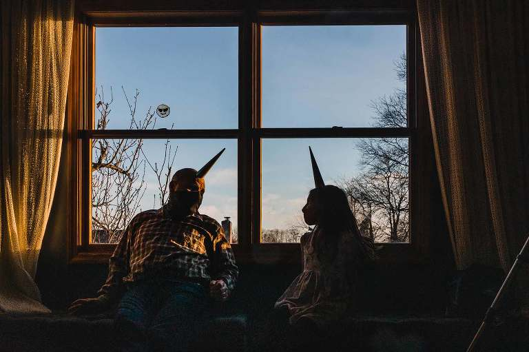 little girl and bald man sit in the window at sunset, framed by the windowpane, wearing birthday party hats and masks