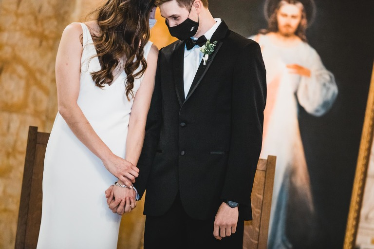 bride and groom in masks on church altar emotionally holding foreheads together and holding hands, in front of painting of jesus blessing them