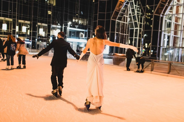 bride and groom ice skating in their wedding dress at night in the city