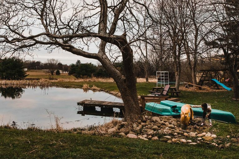 little girl looks under a kayak, standing next to a small pond in a farm backyard. playground and trampoline in the background. pretty light!