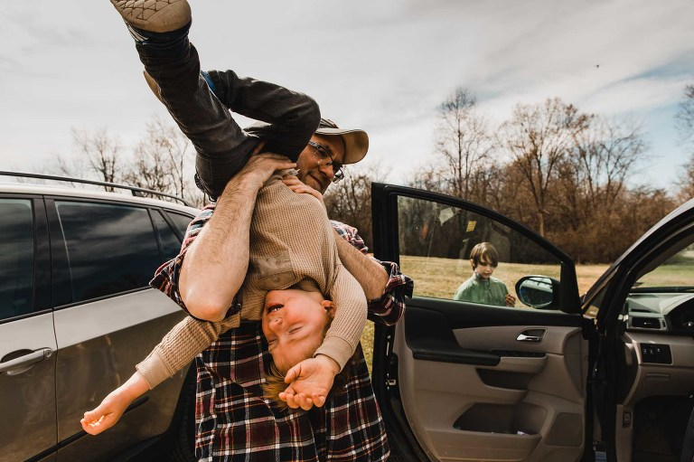 toddler throwing a tantrum, being held upside down by his dad, standing next to the car in a park