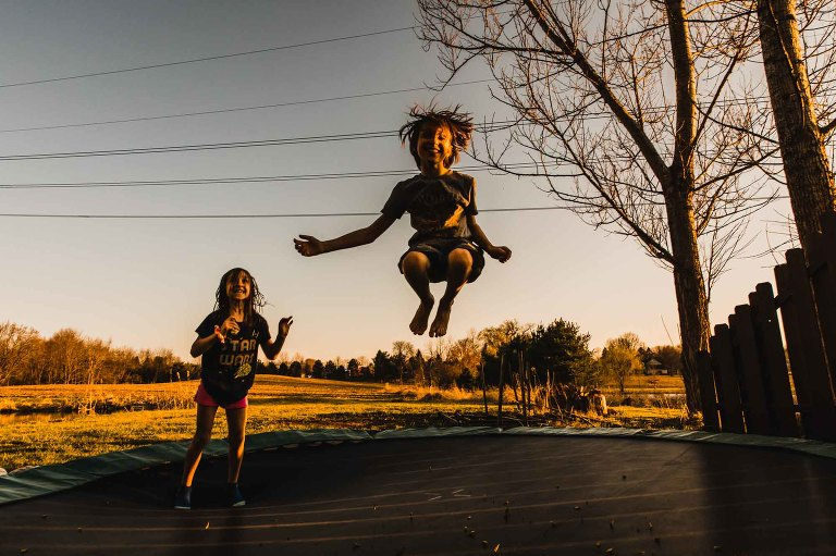 kids jumping on a trampoline at sunset