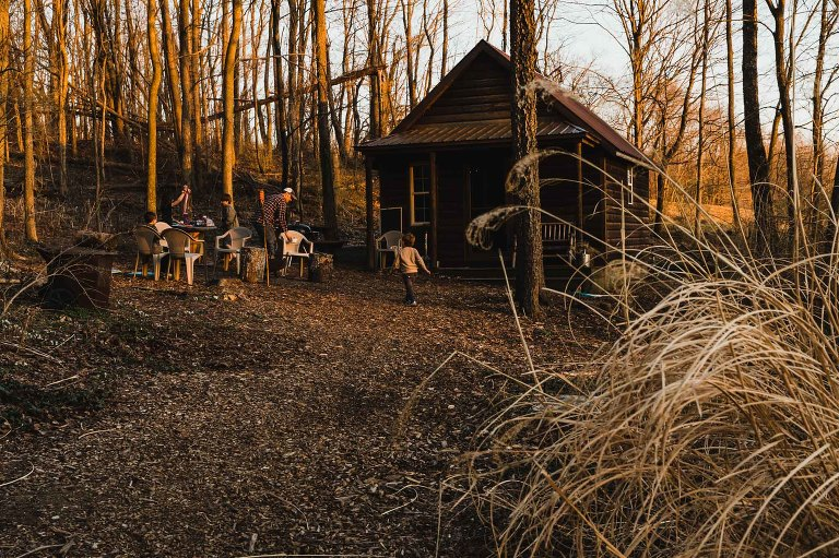 people camping in a cabin at sunset, getting ready for a campfire