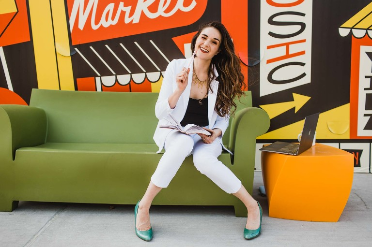 woman sits on green couch surrounded by retro themed colorful mural wall, drawing in a sketchbook and acting silly