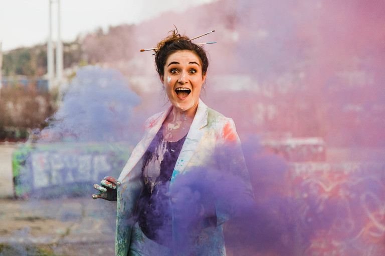 artist is covered and paint surrounded by colorful smoke bombs