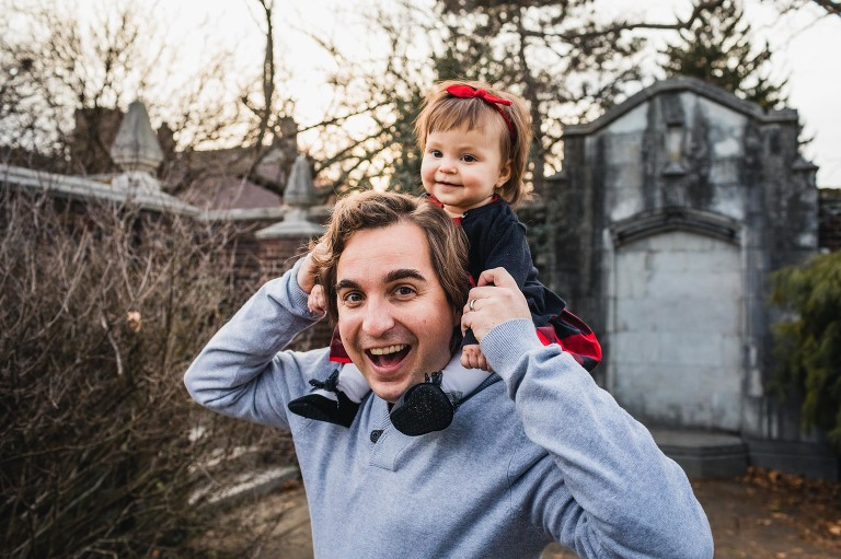 dad holding baby girl on his shoulders and laughing