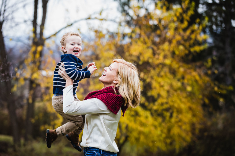 mom throws her son up into the air laughing