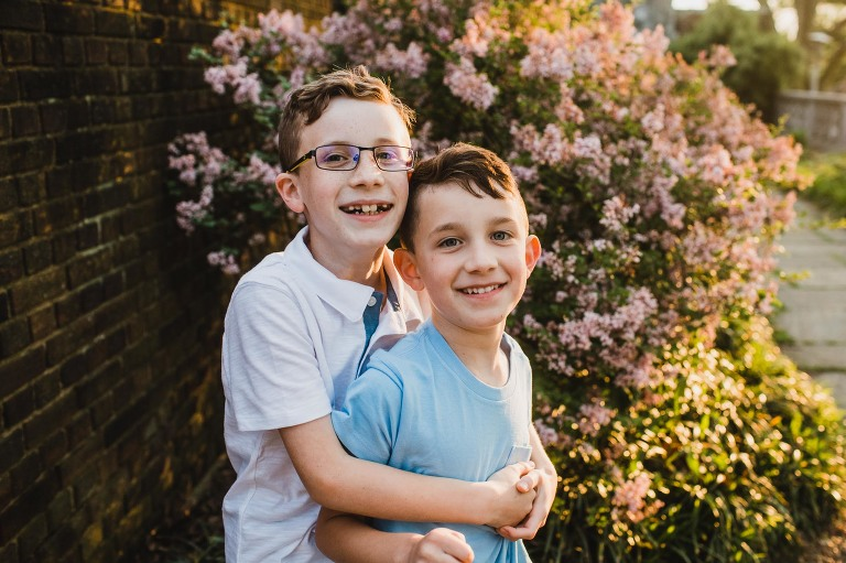 brothers hugging in front of colorful bush in a city park