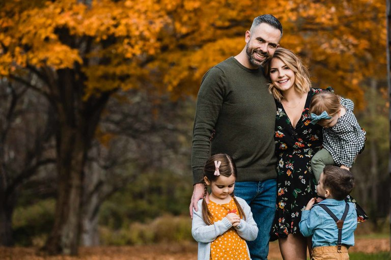 portrait of a family of 5 standing in front of fall foliage in pittsburgh
