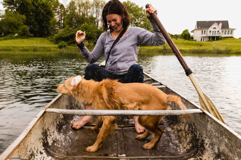 dog shakes water off himself onto his mom, while riding in a boat during their photography session