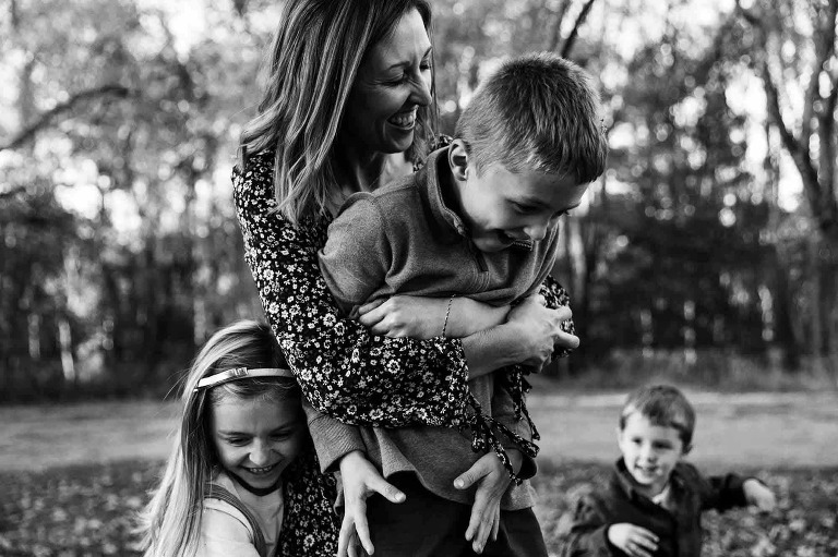 mom hugging and playing with kids outside, black and white photo captured during pittsburgh mini sessions