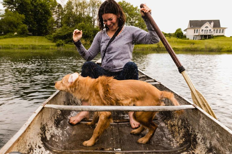 mom rowing a boat on a lake with house in the background, as wet golden retriever dog shakes water all over here, laughing