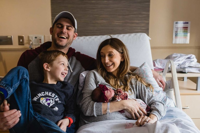 family welcoming newborn at magee hospital in their first family portrait