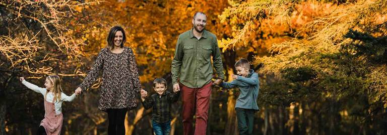 fun family photography of mom dad and kids walking toward the camera, in front of beautiful fall foliage in western pa