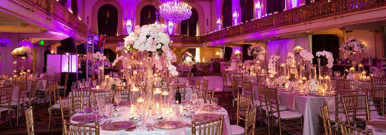 empty room at the omni william penn hotel ballroom, set up with pink uplighting and gold accents with white flower centerpieces