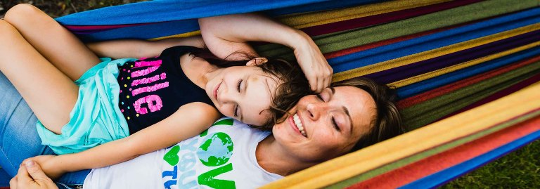 candid picture of mom and little girl snuggling in a colorful hammock