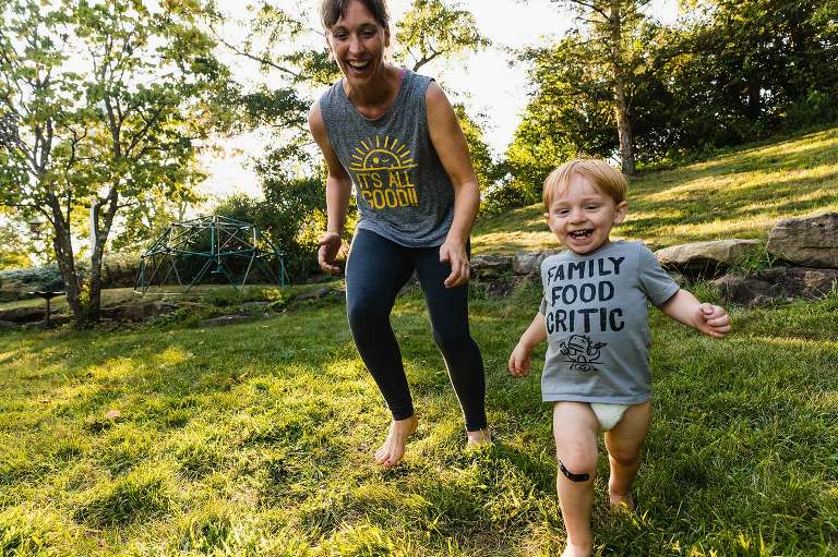 crazy mom chasing her toddler, both laughing hysterically, with beautiful afternoon light
