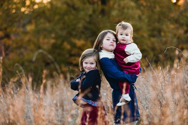 candid pic of kids being silly for their family picture, standing in tall grass at sunset in the fall