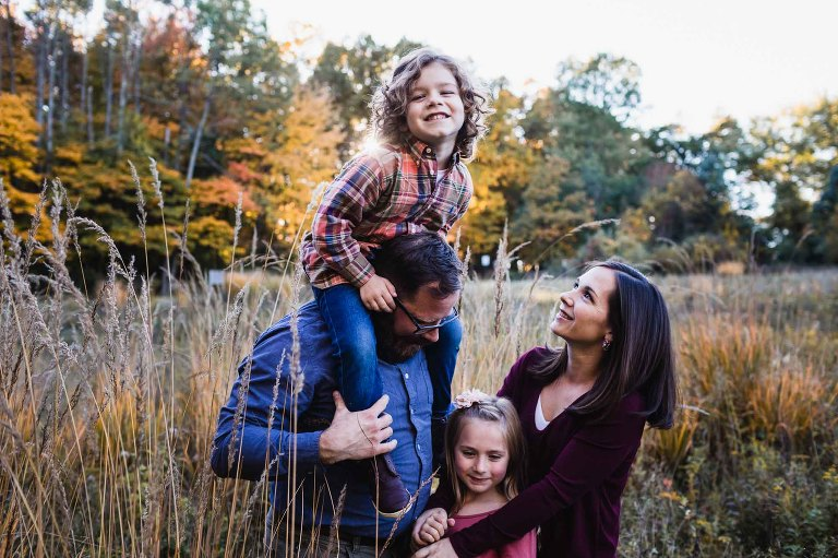 relaxed family picture in the park with fall foliage behind